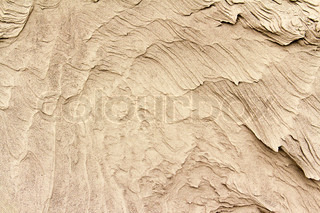 patterns of erosion of sand in the background
