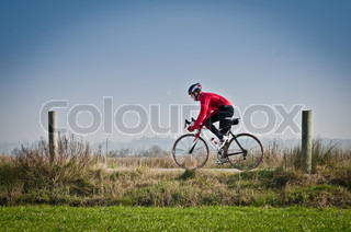 Man on road bike riding down open country road