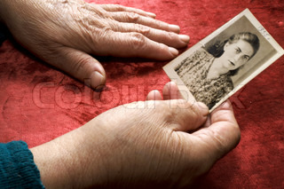 Old hands keep a photo of a young woman