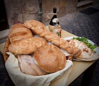 Various loaves in a basket and a bottle of wine seen outside a Roman restaurant