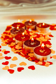 Burning candles heart shaped on a light background