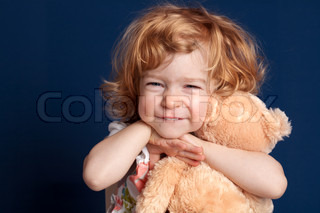 Smiling beautiful child embraces teddy bear