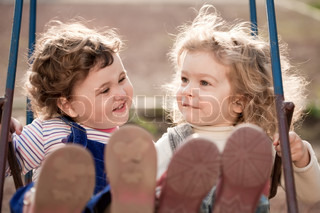 Twin baby sisters playing on swing in autumn park