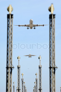 Planes are flying over landing lights in an airport