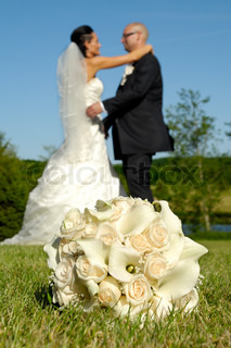 Wedding bouquet in grass in focus and wedding couple in the background