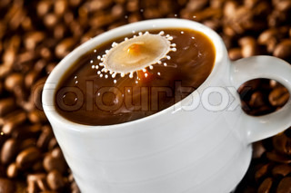 Milk drop falling into a cup of coffee