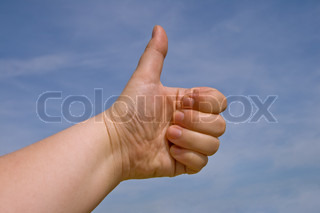 Fist with a thumb up against blue sky
