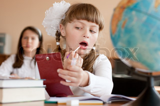 Cute preteen schoolgirl is making make-up during lesson at school