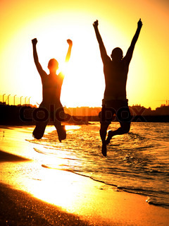 Two happy jumpers on the beach at sunset