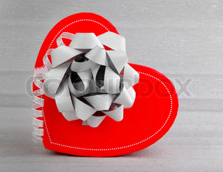 Red heart romantic gift box isolated on silver background, conceptual image of love & celebration