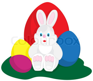 Easter bunny sitting with colored eggs on green
