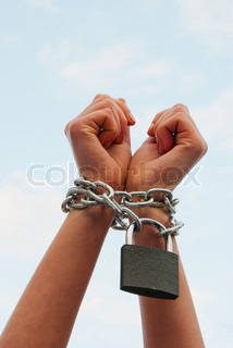 Woman's hands tied up with chains against blue sky