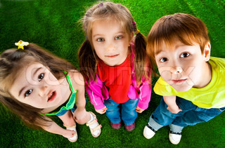 laughing small kids on a grass background