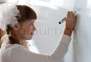 Schoolgirl is writing equation solution on whiteboard