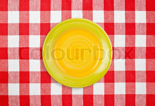 yellow plate on red checked tablecloth