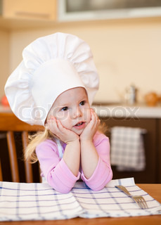 Little cook girl sitting at kitchen table waiting for meal