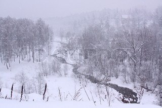 Snowy landscape with blizzard and windy creek