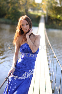 Slender young woman in blue dress standing in the sunshine on a long suspension bridge spanning a river