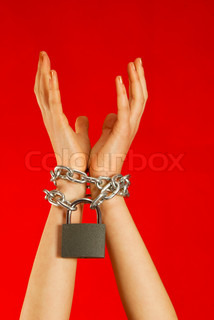 Hands tied up with chains against red background