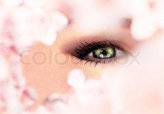 Beautiful abstract green eye surrounded with flowers