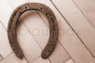 Old lucky horseshoe hanging on the wooden wall (in sepia)