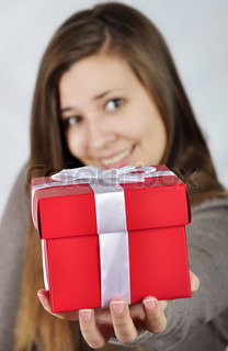Red gift box in hand of young girl Focus on the gift box