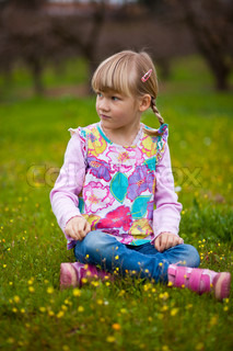 Cute little girl sitting on a green field with flowers