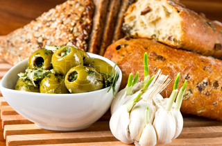 olives and garlic with tasty Italian bread on wooden table