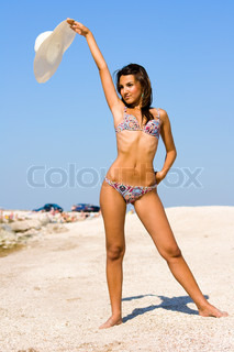 Young beautiful sexy tanned brunette woman with hat and bikini laying on sea beach