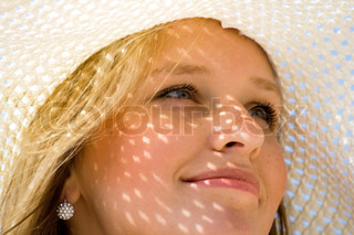 Young girl under hat in summer