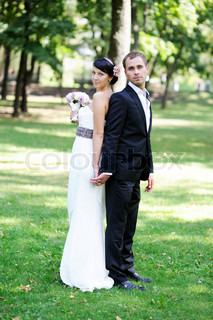 Elegant bride and groom posing together outdoors on a wedding day