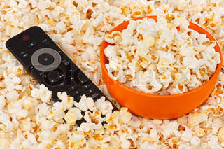 Popcorn in a orange bowl and remote control