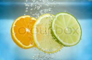 Tangerine lime and lemon slices in blue water with air bubble