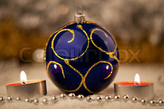 Blue Christmas ball and a candles on the background