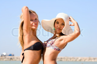Two young girls walk on a beach