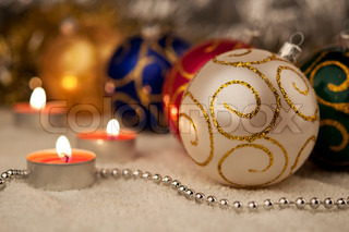 White Christmas ball and a candles on the background