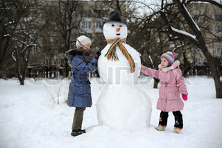 Two little girls are doing great snowman