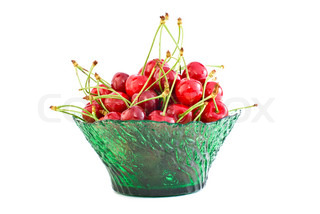 Green glass bowl filled with the red cherries isolated on the white background