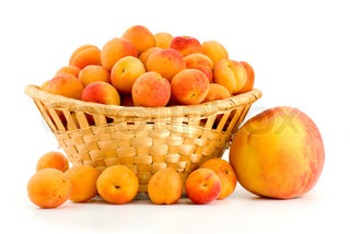 Wicker basket filled with apricots and single peach near isolated on the white background