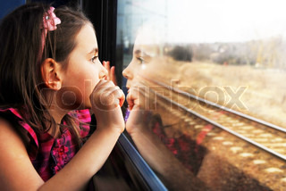 Little girl looking through window. She travels on a train