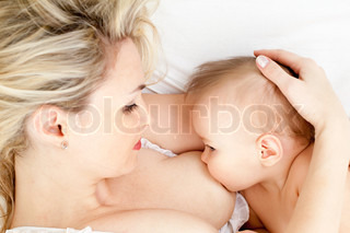 mother breast feeding her child, focus on the child