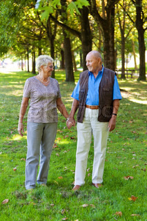 mature senior couple in love walking in a meadow
