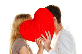 couple in love kissing behind a heart