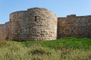 Round tower and wall of medieval castle among grass