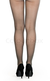 shapely female legs in pantyhose and shoes with heels in the studio on a white background