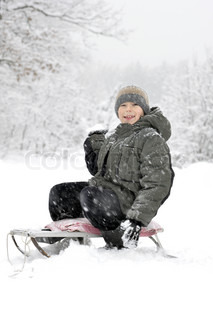 smiling boy on a sled going to throw snowball Walk in the snowy winter woods