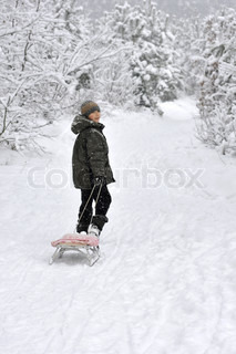 smiling boy walking with sleds in snow-covered winter forest