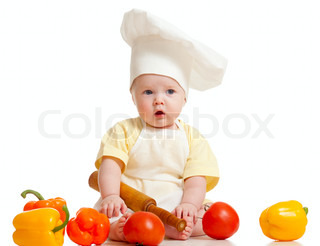 Portrait of a baby wearing a chef hat with healthyfood vegetables, isolated on white