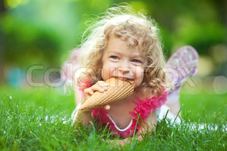 Smiling child eating ice-cream in summer park