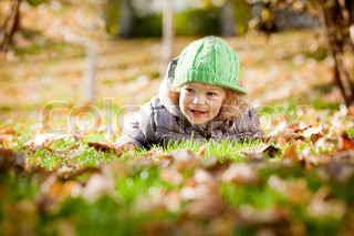 Happy baby girl laying on yellow leaves in autumn park